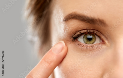 Fotografia vision, beauty and people concept - close up of woman pointin finger to eye