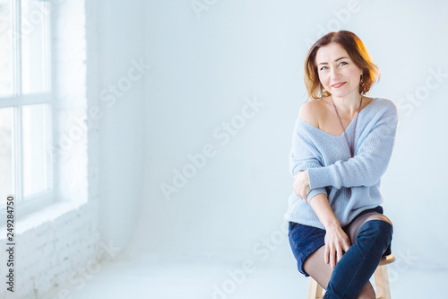 Fotografia  Elegant slim mature woman with bare shoulder in skirt and blue sweater poses on stool in studio, vertical portrait