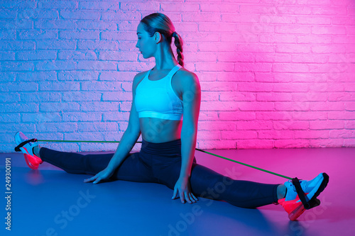 Fotografie, Obraz  Tender young slim gymnast woman in sports clothing stretching with elastic band in front of brick wall in neon lights