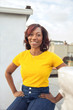 Millennial African American woman wearing yellow poses on an urban rooftop
