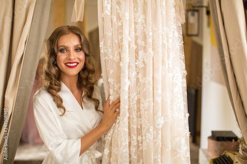 Spoed Foto op Canvas Muziekwinkel Beautiful blonde bride in robe posing near white wedding dress. Morning of the bride.