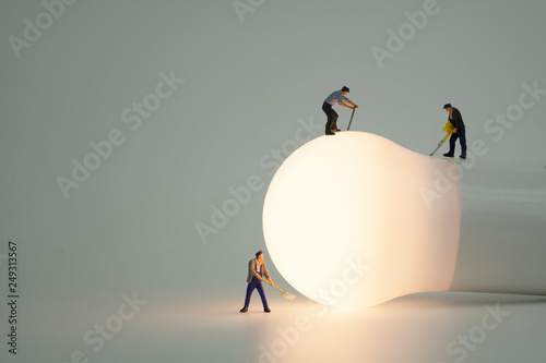 Foto  Miniature people with light bulb