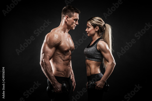 Fotografie, Tablou  Sporty young couple posing on black background
