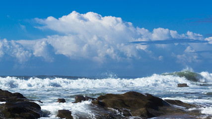 waves with rocks and clouds