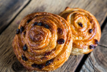 Fresh Buns With Raisins On A Wooden Table