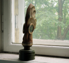 Soviet Military Old Gas Mask With Filter Standing On The Windowsill In The Building
