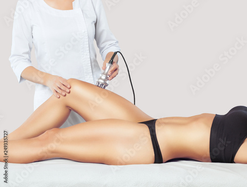 Fényképezés  The doctor does the Rf lifting procedure on the legs, buttocks and hips of a woman in a beauty parlor
