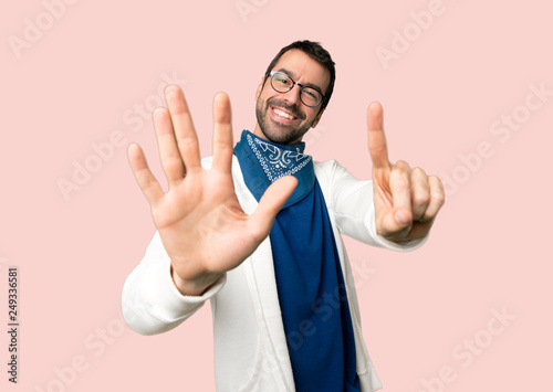 Handsome man with glasses counting six with fingers on isolated pink background Poster Mural XXL