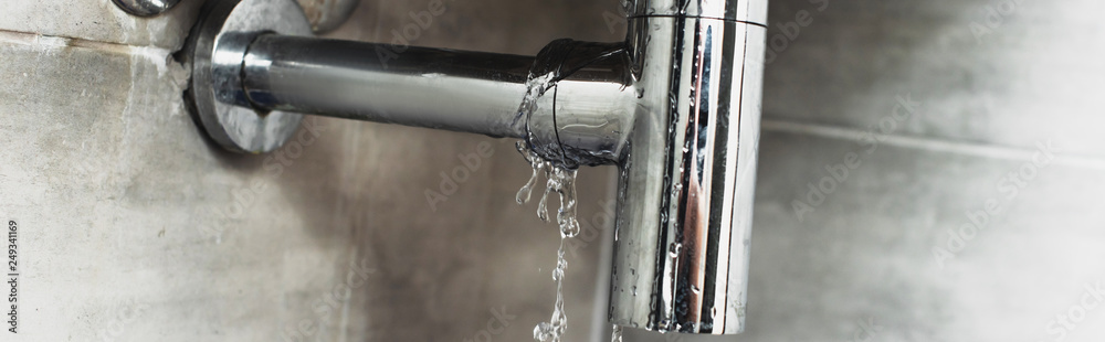 Fototapeta Damaged steel pipe with water drops on grey background