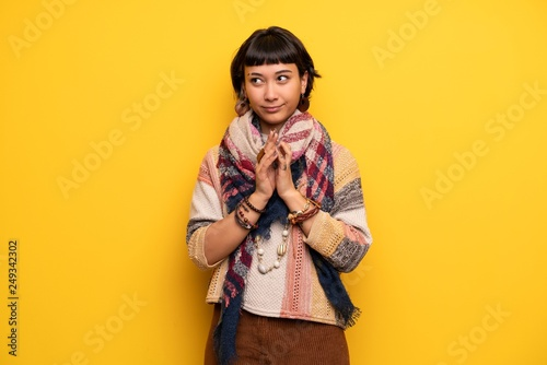 Fotografie, Obraz  Young hippie woman over yellow wall scheming something