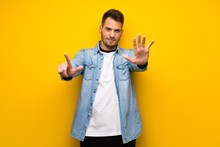 Handsome Man Over Yellow Wall Counting Seven With Fingers