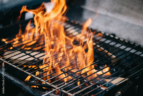 Foto op Plexiglas Brandhout textuur burning firewood with flame through bbq grill grates