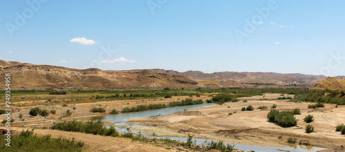 river in the middle of the desert of Iran with mountains and grass and the horizont with cloudy sky