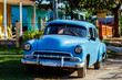 Blue vintage Cuban car parked in front of tropical home in rural Cuba