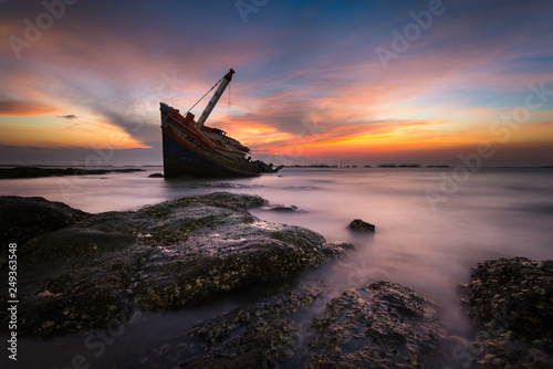 Foto op Canvas Schipbreuk An old shipwreck or wrecked boat abandoned stand on beach