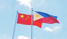 Philippines And China, Two Flags Waving Against Blue Sky. 3d Image