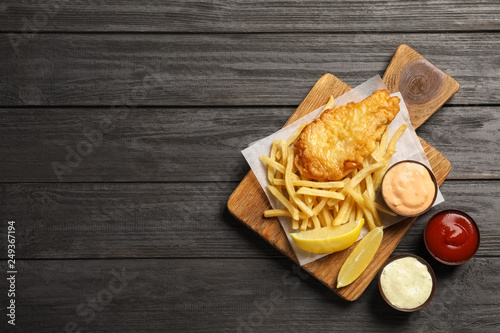 Cuadros en Lienzo  British traditional fish and potato chips on wooden background, top view with sp