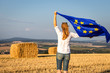 Leinwanddruck Bild - Woman holding waving european union flag outdoors. Countryside in Europe