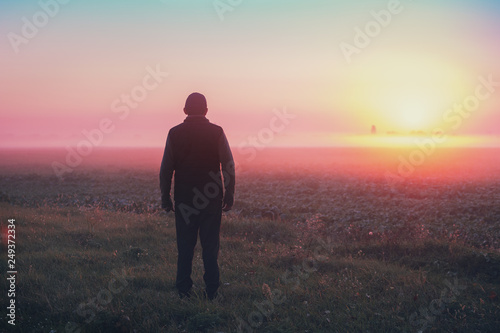 Fotografía  A man stands in the field in the early morning and looks at the sunrise