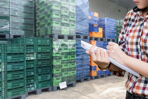 Photo  Close-Up shooting hand of quality control with paper sheet checking plastic pallet and empty crates for transportation to goods