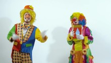 Two Funny Circus Clowns Playing With A Red Glossy Box Throwing It To The Air