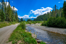 Gravel Road With Stream And Mountains