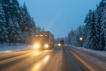 Cars Drive With Headlights On The Winter Road In A Snow Storm In The Twilight When Snow Is Flying. Concept Of Driving In The Dangerous Conditions With Bad Visibility On The Winter. Image With Motion