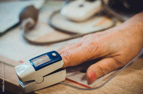 Pulse oximeter on the finger and hand of an old woman in the