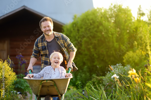 Fotografía  Happy little boy having fun in a wheelbarrow pushing by dad in domestic garden on warm sunny day