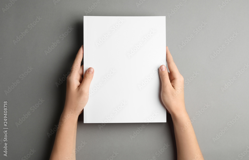 Fototapeta Woman holding brochure with blank cover on grey background, top view. Mock up for design