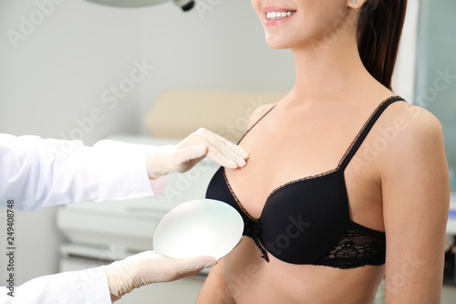 Fototapeta Doctor showing silicone implant for breast augmentation to patient in clinic, closeup