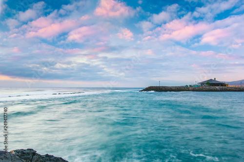 Fotografia  Purple clouds during sunrise over beach bar at rocky shore