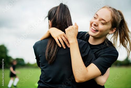 Fotografie, Obraz  Female football players hugging each other