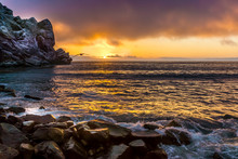 Morro Bay Sunset With Gull Flying And Waves Breaking On Rocks