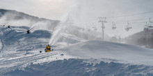 Snow Guns And Ski Lifts On Snow Covered Mountain