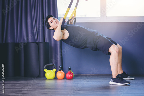 Fotografía  Fit man doing pull up exercise for arm muscle with TRX fitness straps in the gym
