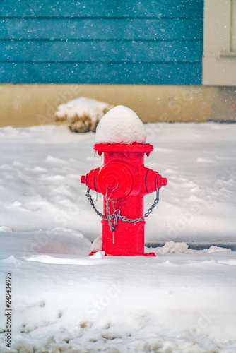 Valokuva  Vibrant red fire hydrant against powdery snow