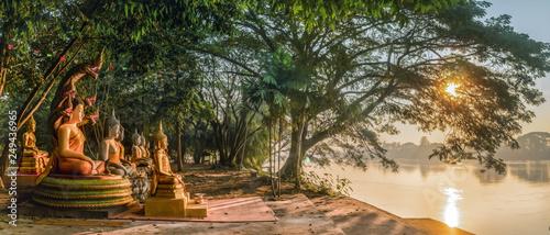 Carta da parati  Buddha statues near river bank during sunrising