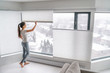 Leinwanddruck Bild Woman opening home curtains in urban condo. Modern top down bottom up privacy cellular shades on apartment window keeping heat in winter with honeycomb blind curtain. Cordless pleated shades.