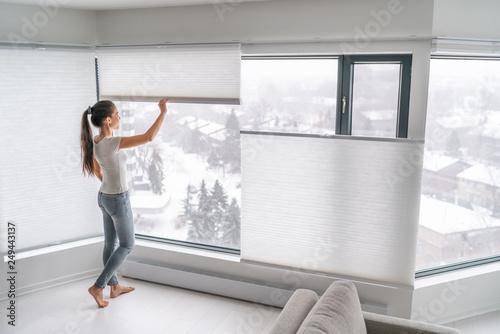 Vászonkép Woman opening home curtains in urban condo