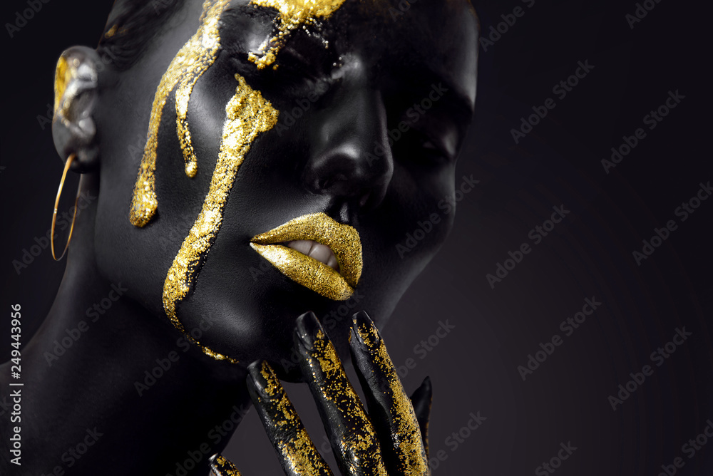 Fototapeta Young woman face with art fashion gold makeup. An amazing model with black and gold creative makeup. Closeup portrait