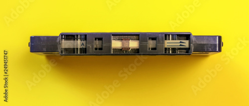 Top down view, start of old audio tape in cassette on yellow board - 249451747