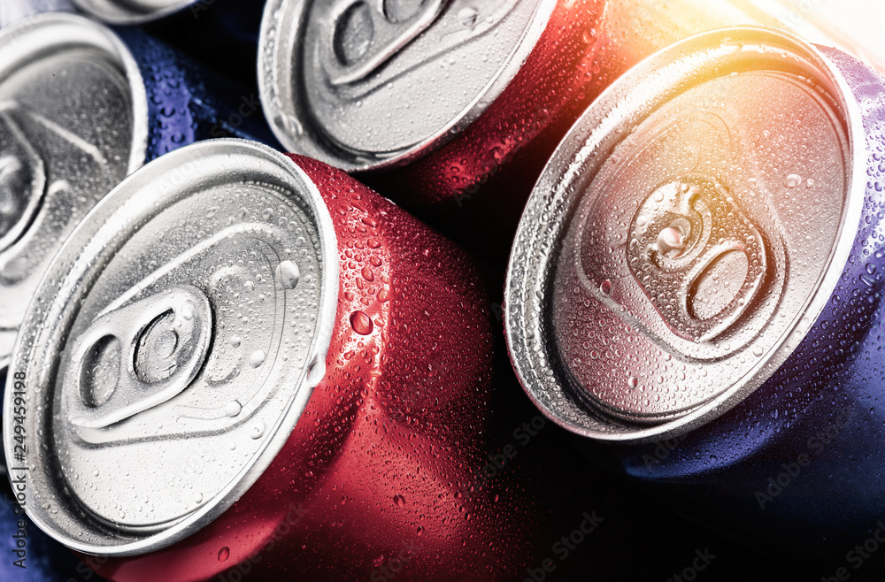 Fototapeta Red and blue cans of soft drinks with water drops.