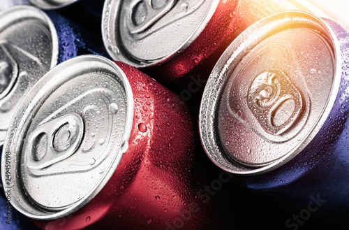Photo  Red and blue cans of soft drinks with water drops.