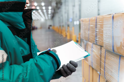 Fotomural  Hand of worker with clipboard checking goods in freezing room or warehouse