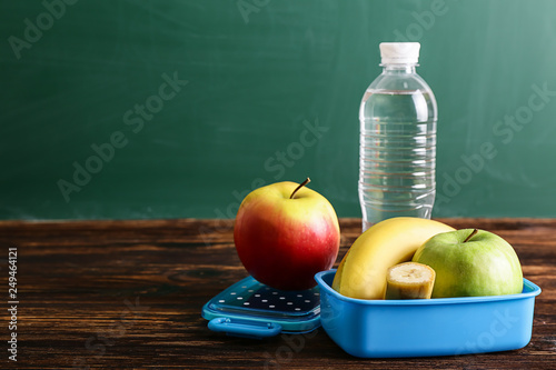 Fotografia School lunch box with tasty food and bottle of water on table