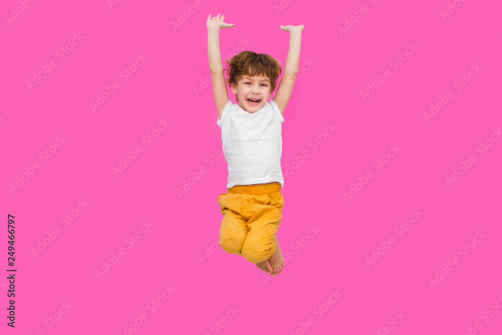 Fototapety, obrazy: Cheerful little boy  jumping on a pink background