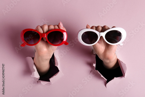 Female hands with stylish sunglasses on color background Poster Mural XXL