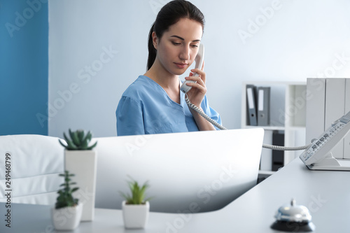 Fotografia Female receptionist talking by phone in clinic