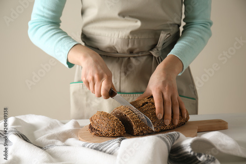 Fotografie, Obraz  Young woman cutting fresh bread at table